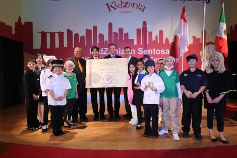 Kids joined by (From left) YM Tunku Dato' Ahmad Burhanuddin, Managing Director and Chief Executive Officer of Themed Attractions and Resorts Sdn Bhd; Tunku Ali Redhauddin ibni Tuanku Muhriz, Director of Themed Attractions and Resorts Sdn Bhd; Mike Barclay, Chief Executive Officer of Sentosa Development Corporation; and Xavier López Ancona, President and Chief Executive Officer of KidZania with the 'Grant of Privilege'.